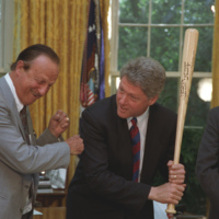 President Clinton poses with a baseball bat